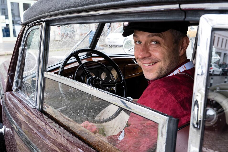 Einer der vielen Teilnehmer der Oldtimer-Rallye Elbflorenz auf dem Obermarkt in Görlitz in seinem Auto.