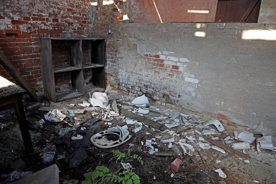 Im Inneren des einstigen Toilettenhauses liegt Müll und zerschlagene WC-Becken.