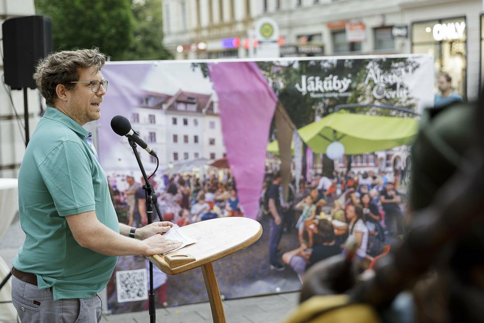 Benedikt Hummel, Geschäftsführer des städtischen Kulturservice, spricht auf der Berliner Straße/Ecke Dr.-Friedrichs-Straße vor einem Altstadtfest-Plakat.