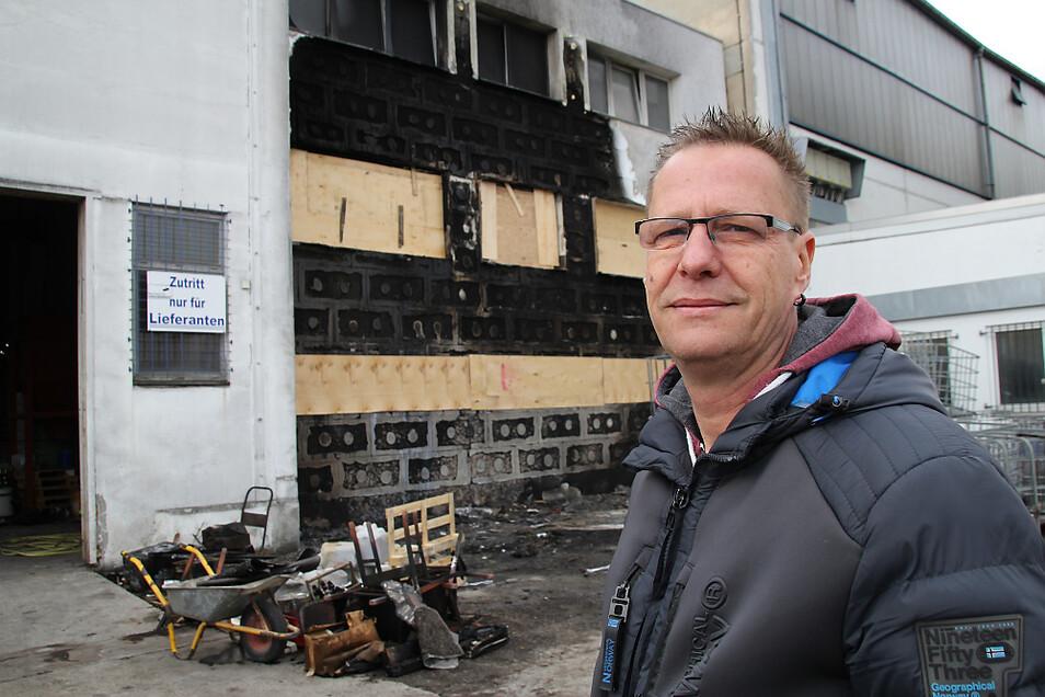 Dirk Lehmann, Inhaber der Firma Hoyo im Hoyerswerdaer Industriegelände, steht vor dem vom Brand beschädigten Gebäudeteil. Die Fassade ist rußgeschwärzt. Zwei Fensterzeilen wurden provisorisch mit Sperrholz-Platten gesichert.