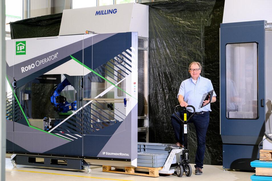 Ralf Hock, Geschäftsführer von Industrie-Partner Coswig, an einer Werkzeugmaschine, die von einem in der Firma entwickelten Roboter bedient wird.