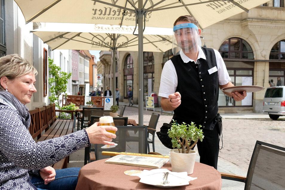 Kellner Tony Kiesling vom Meißner Ratskeller serviert jetzt mit Visier vorm Gesicht. Gast Evelin Enke muss aber keinen Schutz tragen.