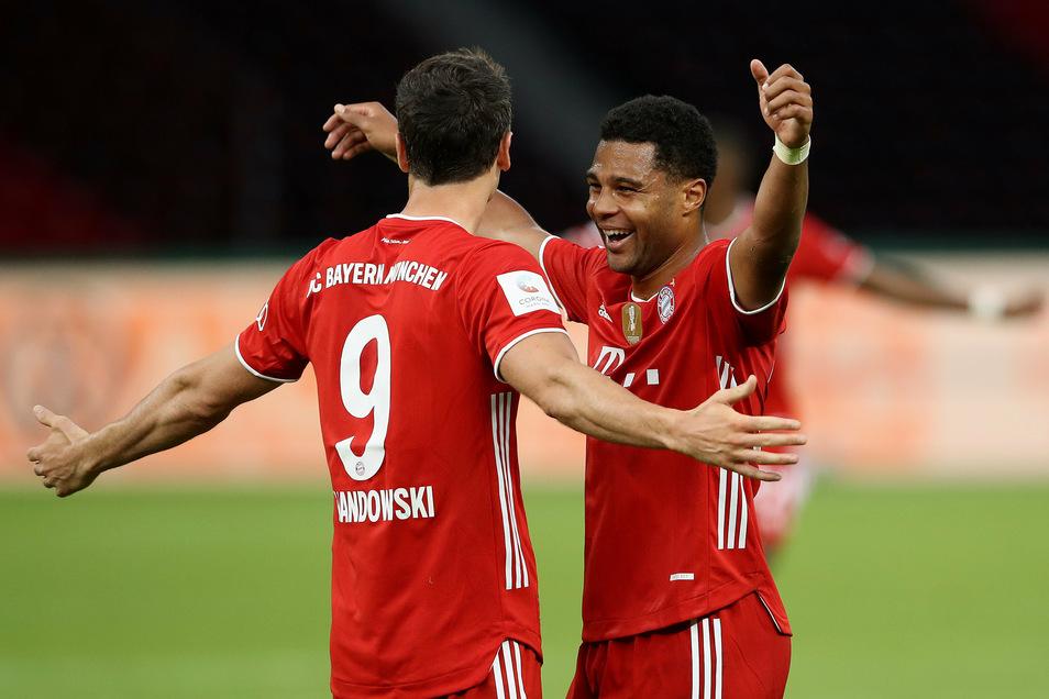 Die Bayern-Torschützen Robert Lewandowski (links) und Serge Gnabry feiern den Münchner Pokalerfolg.