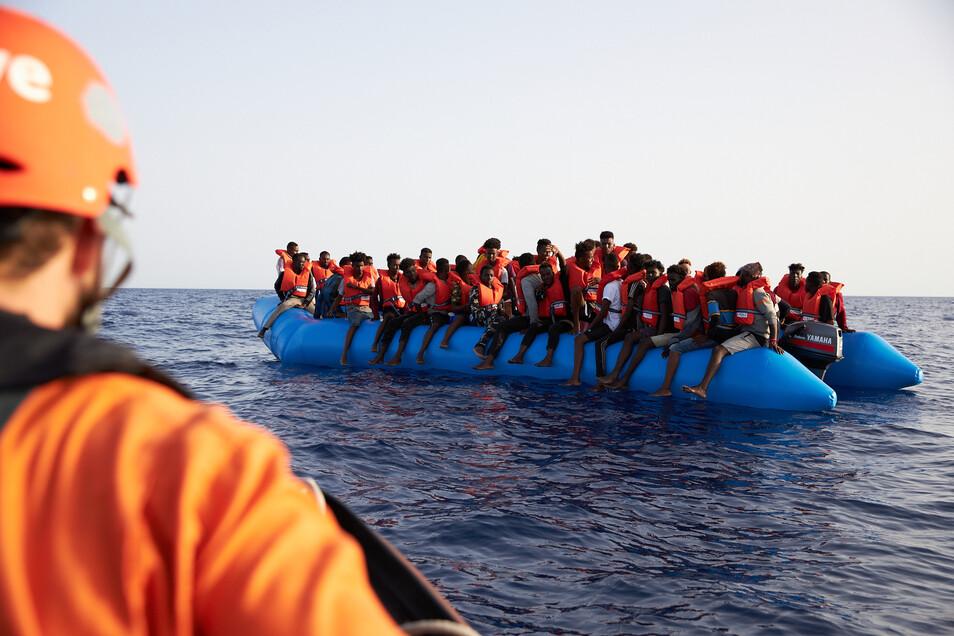 Ein Seenotretter von Sea-Eye (l) fährt zu einem völlig überladenem Flüchtlingsboot im Mittelmeer.