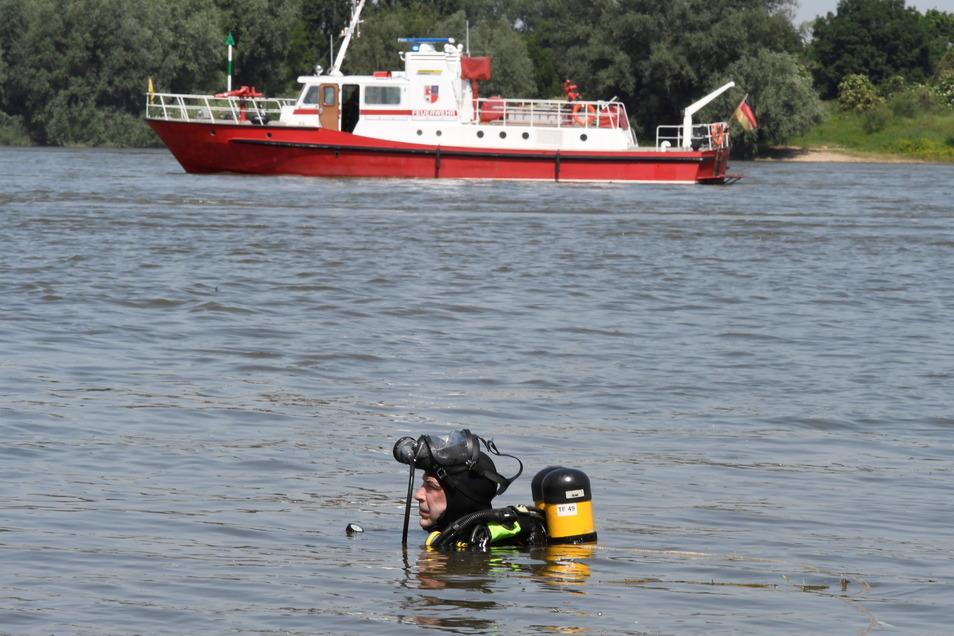 Ein Taucher der Feuerwehr sucht nach zwei vermissten Mädchen, die am Mittwoch Rhein ein erfrischendes Bad nehmen wollten.