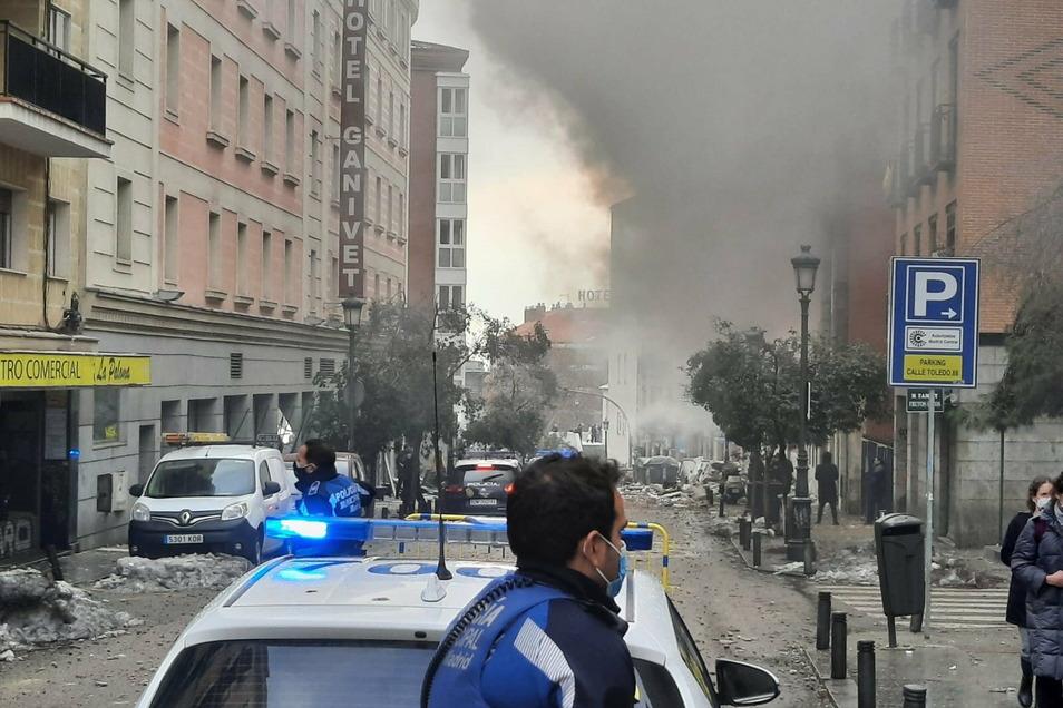Ein Polizeiauto und ein Polizist stehen auf der Toledo Straße in Madrid nach einer starken Explosion.