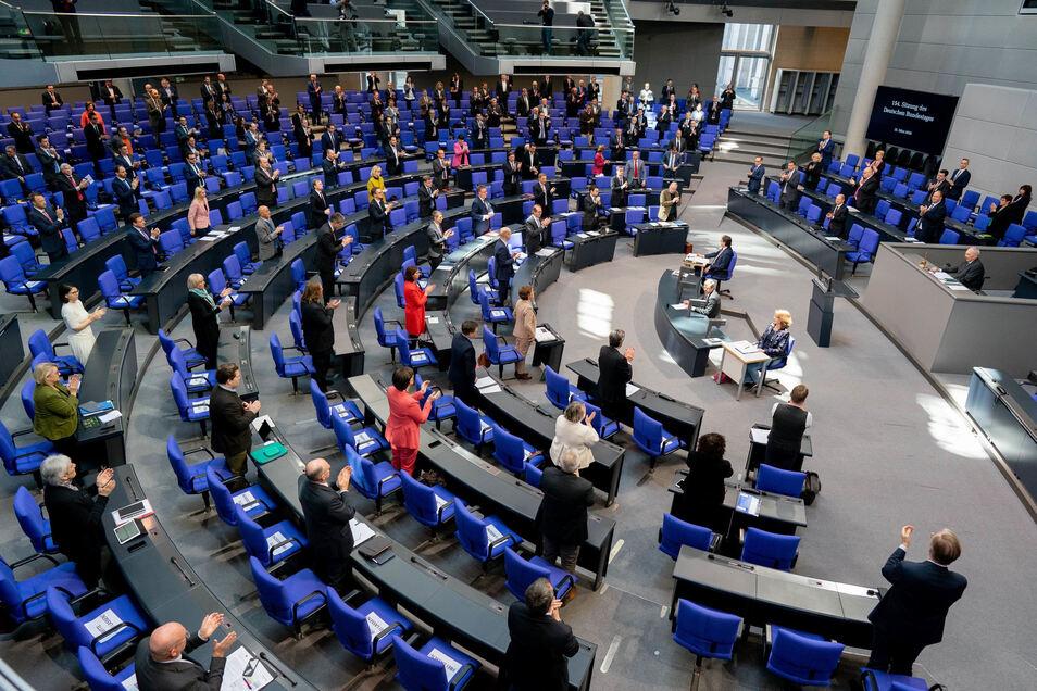 Die Bundestagsabgeordneten erheben sich zum Dank für alle Helfenden in der Corona-Krise zu Beginn der 154. Sitzung des Bundestages von ihren Plätzen.