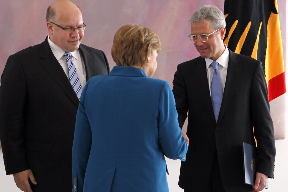 Angela Merkel (CDU) gibt nach der Ernennung des neuen Umweltministers Peter Altmaier im Mai 2012 Norbert Röttgen die Hand.