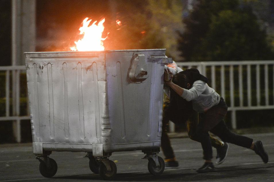 Demonstranten schieben während einer Kundgebung eine brennende Mülltonne in Richtung der Polizei