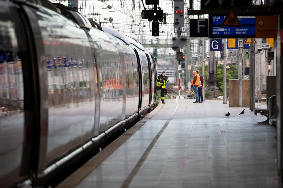 Einsatzkräfte stehen am ICE im Kölner Hauptbahnhof, bei dem es zu einer Rauchentwicklung gekommen war.