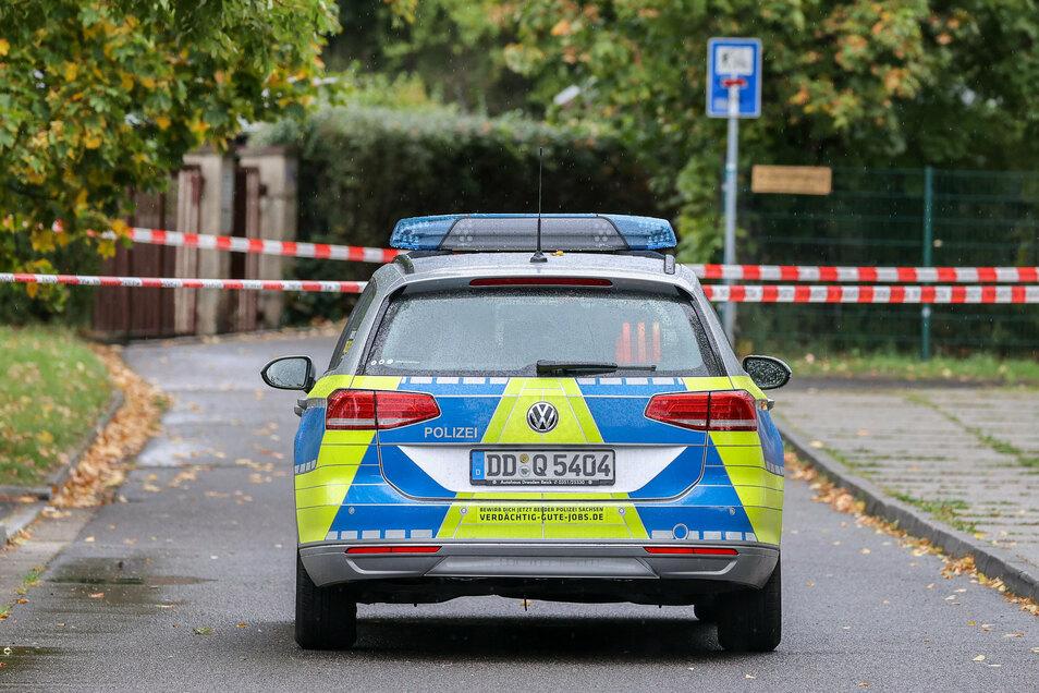Ein Polizeifahrzeug steht an einer Absperrung im Leipziger Stadtteil Paunsdorf. Die Polizei sucht mit einem Großeinsatz nach einem Mann, der mehrfach versucht haben soll, Kinder zu entführen.
