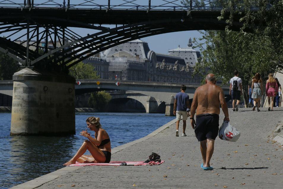 Eine Frau genießt am vergangenen Freitag das sonnige Wetter am Seineufer in Paris. Seit dem heutigen Montag gilt in der französischen Hauptstadt eine Maskenpflicht an zahlreichen öffentlichen Orten im Freien.