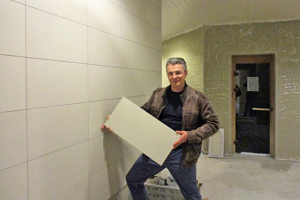 Sbf-Geschäftsführer Titus Reime zeigt die neuen Fliesen. Eine hält er in der Hand, andere sind schon an der Wand.