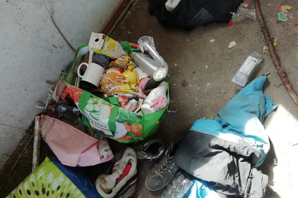 In wenigen Räumen sind die Fenster noch in Ordnung. Schuhe, Lebensmittel und Geschirr weisen darauf hin, dass die Wohnung bis vor Kurzem als Unterschlupf diente.