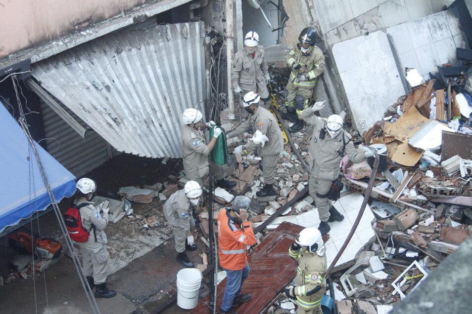 Rettungskräfte arbeiten in den Trümmern des eingestürzten Gebäudes.