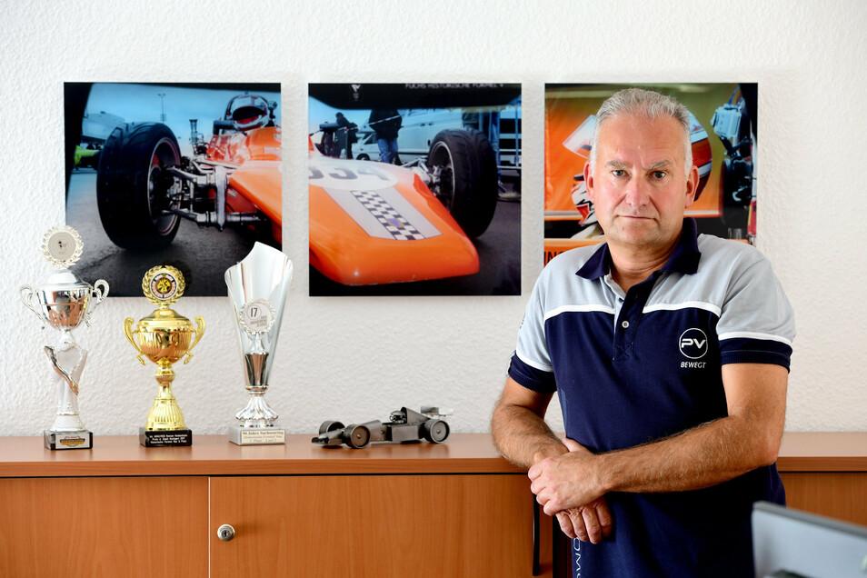 Ingolf Sieber mit Fotos des Rennwagens an der Wand seines Büros.