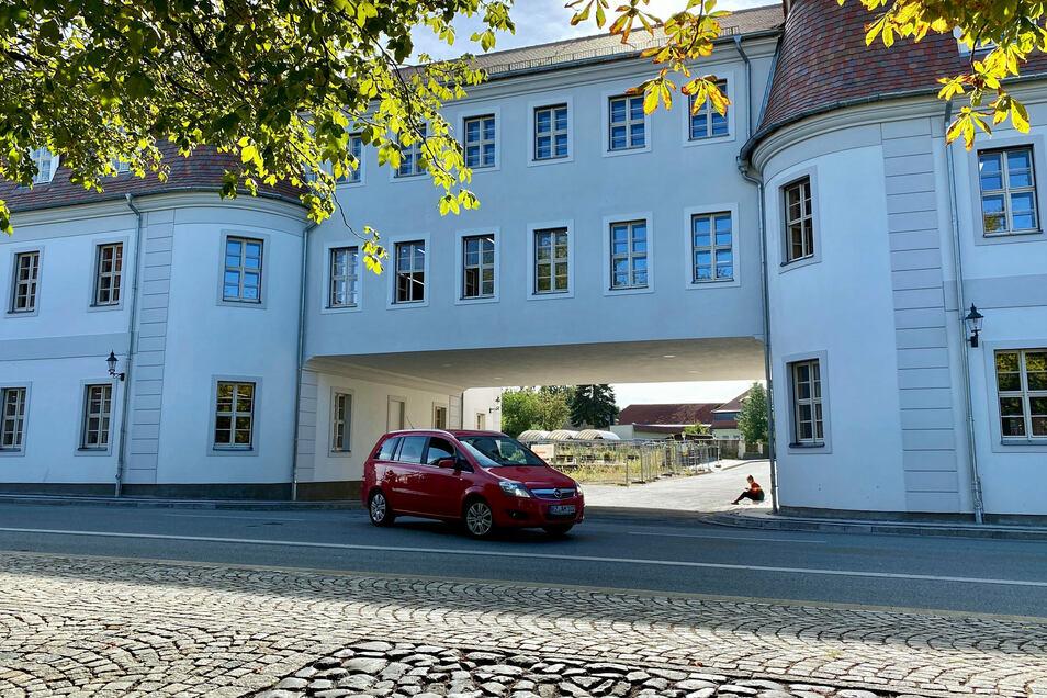 Blick auf die straßenseitige Fassade des Neubaus, der den historischen Bauten in Herrnhut angepasst ist. Durch den Durchgang schaut man auf den künftigen Campus.