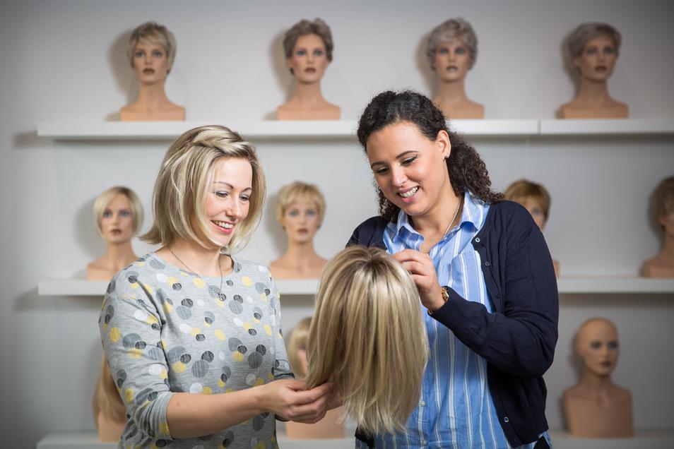 Friseurmeisterin Stefanie Unglaube (r.) zeigt Kundin Anne Schörnig eine Perücke, die dem Modell auf ihrem Kopf gleicht. Mindestens einmal im Jahr muss die Krankenschwester, der wegen einer Krankheit die Haare ausgefallen sind, die Perücke wechseln.