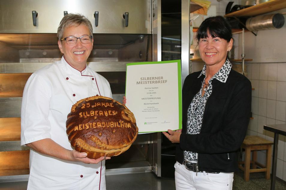 Jana Klässig von der Handwerkskammer Chemnitz überreichte den silbernen Meisterbrief an Bäckermeisterin Karina Garten von der Bäckerei Nowack in Grünlichtenberg. Die hat zur Feier des Tages extra ein besonderes Brot gebacken.