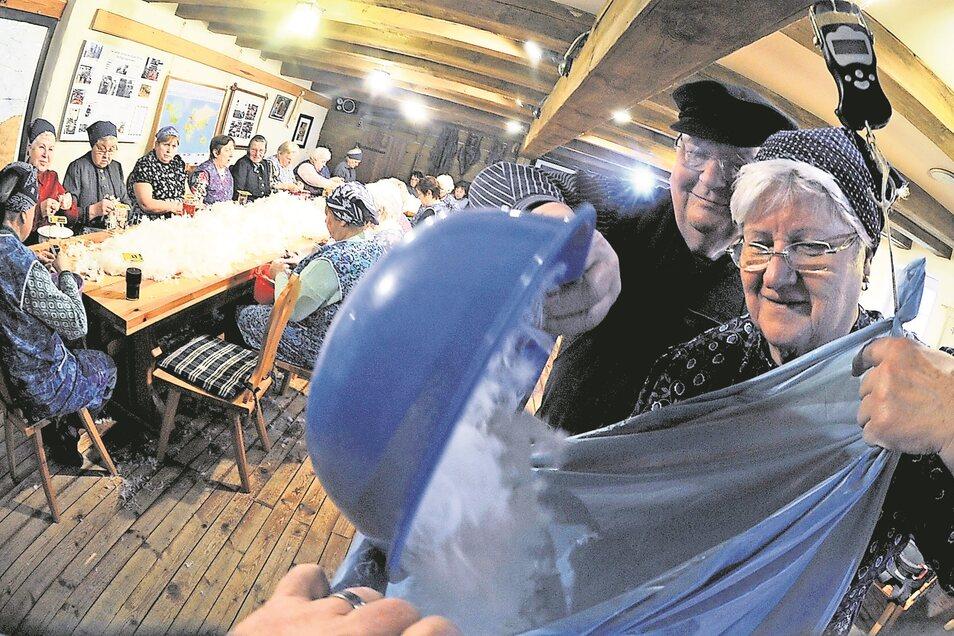 Die Vereinsmitglieder Marlies Nagorka und Manfred Richter füllen ein Kopfkissen mit Daunen.