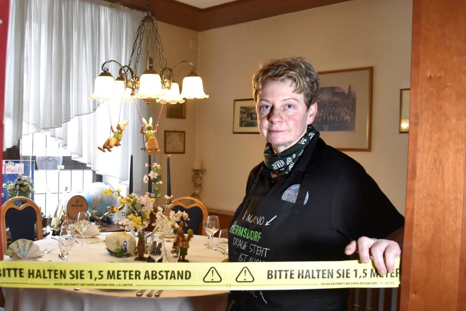 Jana Richter vom Gasthof Hermsdorf hat in einer Ecke eine Tafel gestaltet und mit Absperrband von Rest des Raumes isoliert. Der Gast kann sich hier ansehen, wie es vor Corona einmal in Gaststuben am Tisch ausgesehen hat. Heute bietet sie Essen zum mitnehm