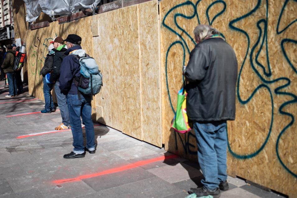 Obdachlose stehen vor einer Hamburger Kneipe und warten auf die Verteilung von Kleidung, Suppe und anderen Lebensmitteln.