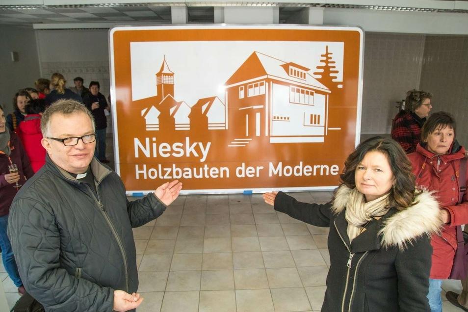 Die Nieskyer Oberbürgermeisterin Beate Hoffmann (rechts) und Pfarrer Krystian Burczek zeigen das Autobahnschild für Niesky – um das engagiert gekämpft wurde.
