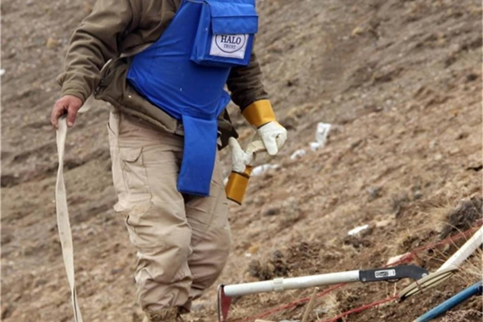 Zum Schutz trägt der Minenräumer eine schwere Splitterschutzweste und ein Visier vor dem Gesicht.