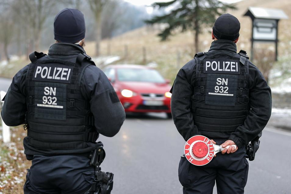 Beamte der Bereitschaftspolizei kontrollieren am Ortsrand von Seiffen die einfahrenden Fahrzeuge.