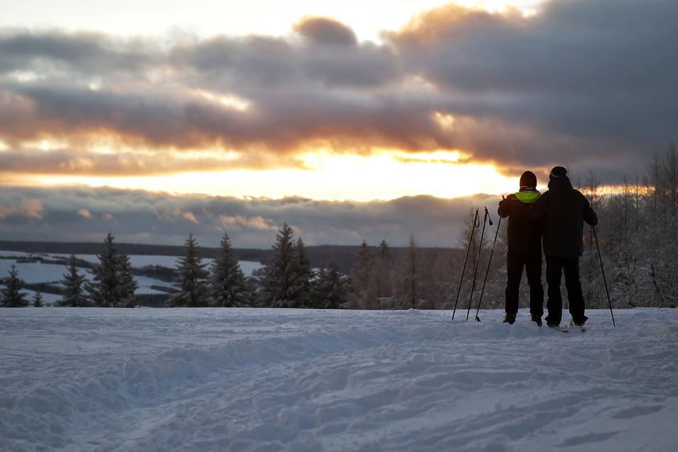 Was für ein Blick: Zwei Skifahrer beobachten den Sonnenuntergang in Schellerhau.