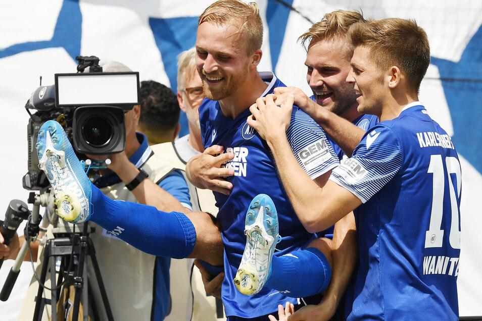 Die Karlsruher (l.-r.) Philip Hofmann, Lukas Grozurek und Marvin Wanitzek bejubeln den Treffer zum 2:1 durch Eigentor des Dresdners Dzenis Burnic.