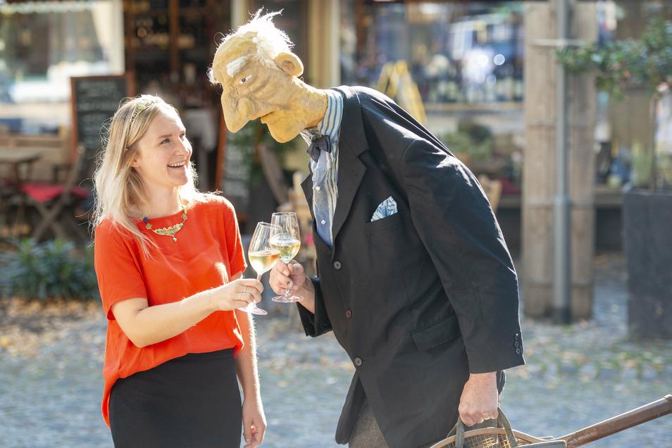 Die Jessener Weinprinzessin Theresa Zwicker und die Radebeuler Kunstfigur Arnold Boeswetter alias Wolfgang Lasch stoßen auf das bevorstehende Weinfestwochenende vom 25. bis 27. September 2020 an.