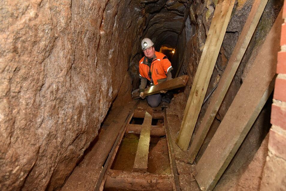 Mitarbeiter Silvio Lehmann reißt im Zinnwalder Bünaustollen alte Bohlen aus dem Besucherfahrweg, um sie durch neue zu ersetzen.