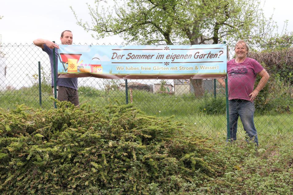 """Heiko Thierbach (links) und Günter Glodek zeigen ein Werbebanner, mit dem die Gartenanlage """"Am Wiesengrund"""" in Döbeln Interessenten anlocken will."""