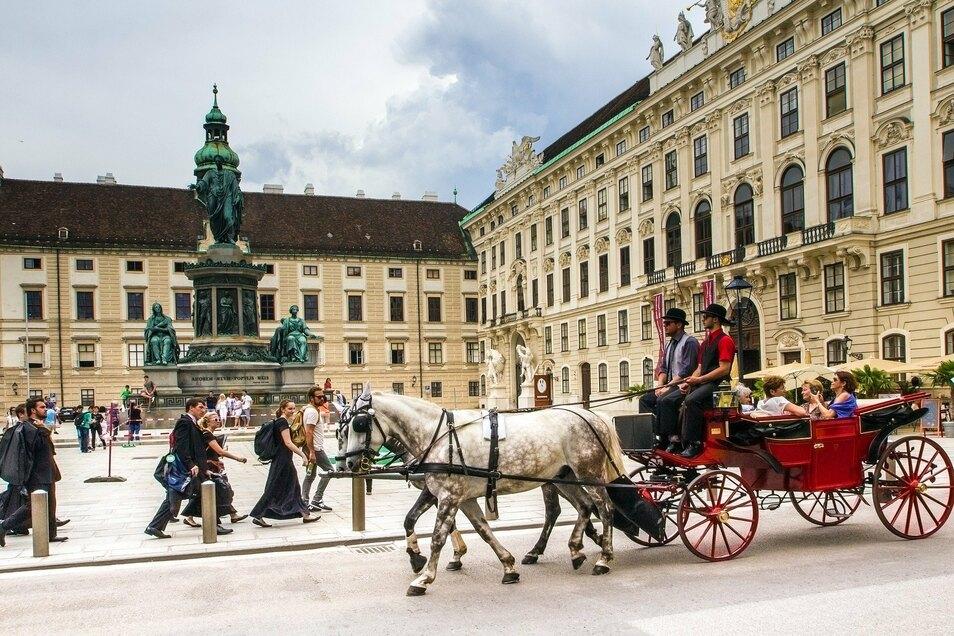 Ein Fiaker fährt Touristen während einer Stadtrundfahrt in einer Pferdedroschke durch Wien.