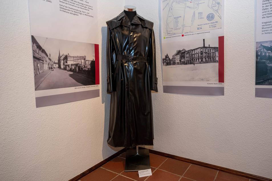 Ein schwarzer Mantel aus Igelit. Dieser ist sehr oft getragen worden, da im inneren deutliche Spuren sichtbar sind.