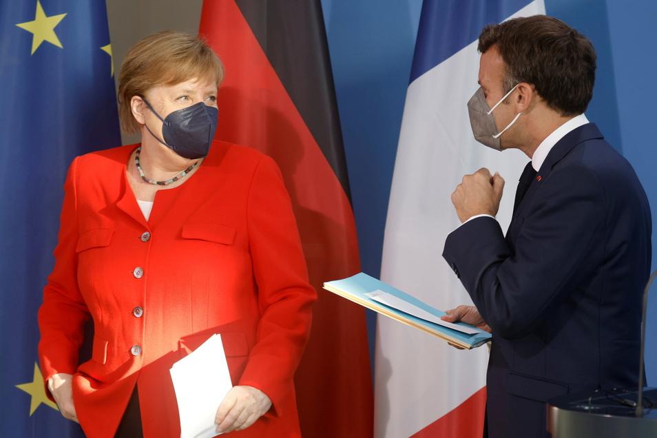 Bundeskanzlerin Angela Merkel (CDU) und Frankreichs Präsident Emmanuel Macron tragen Masken, nachdem sie ein Statement abgeben haben.
