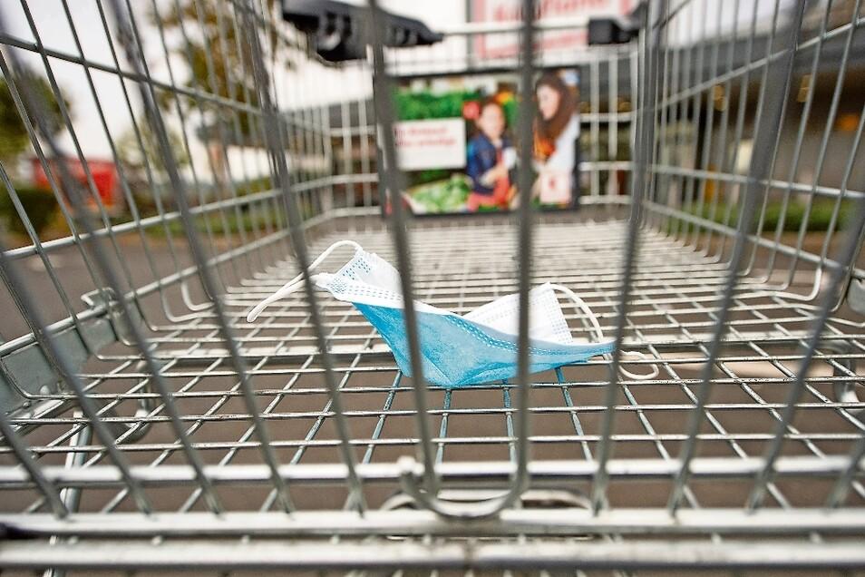 Eine Mund-Nasen-Maske liegt in einem Einkaufswagen vor dem Supermarkt von Kaufland in Radebeul. Drin im Markt muss die Maske aufgesetzt werden. Hinweise darauf gibt es mehrere vor dem Supermarkt.