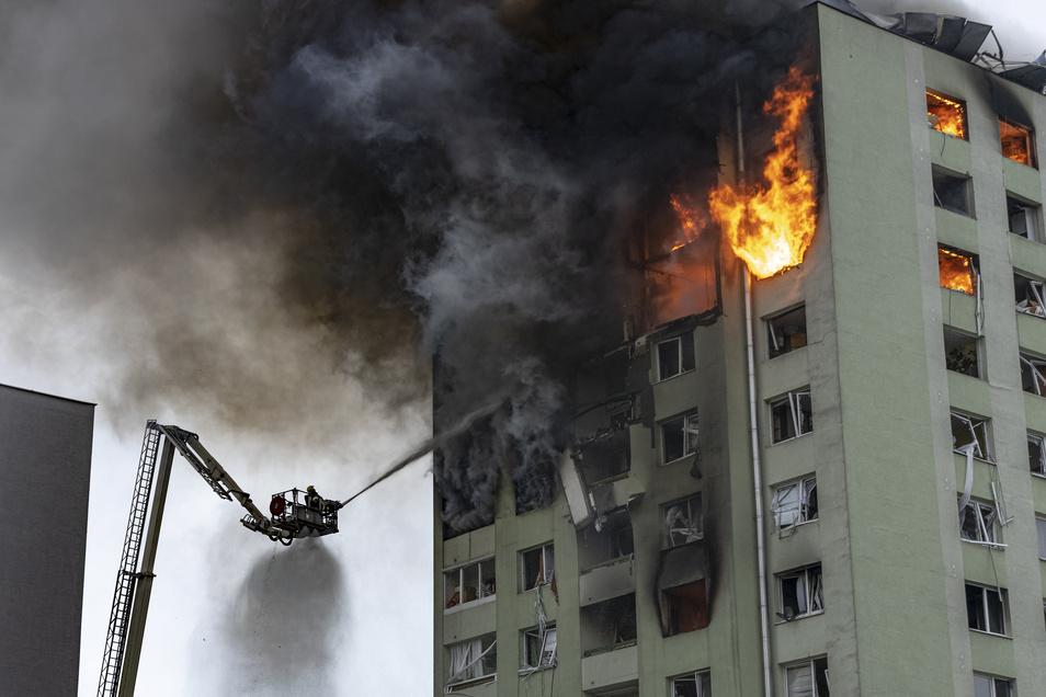Feuerwehrleute löschen einen Brand in einem 12-stöckigen Mehrfamilienhaus, das durch eine Gasexplosion schwer beschädigt wurde.