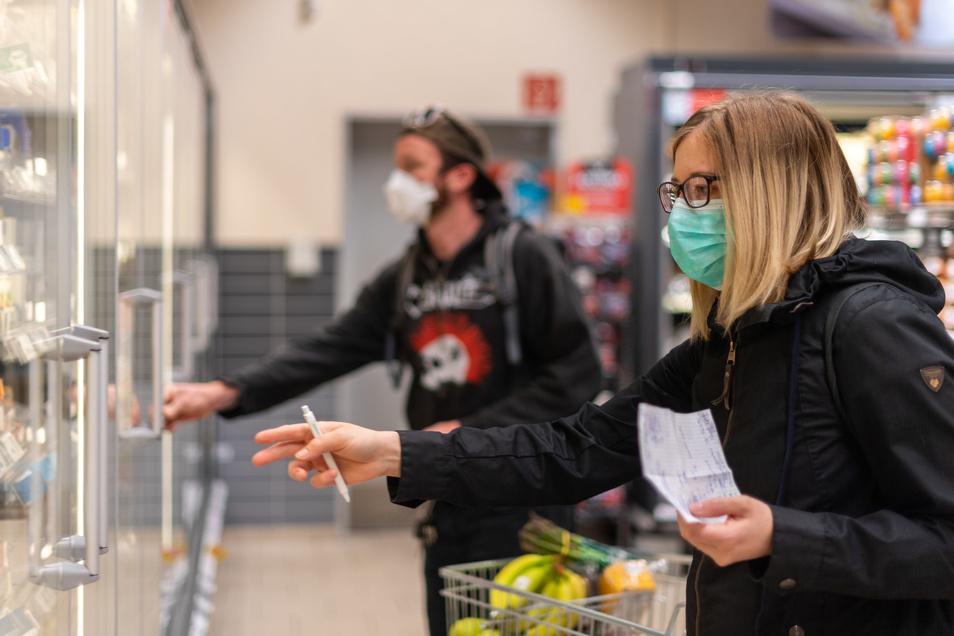 Kunden gehen in einem Supermarkt einkaufen und tragen dabei Mundschutz. Am Montag wurden die ersten Corona-Auflagen schrittweise gelockert, in Sachsen gilt im Einzelhandel jedoch eine Mund-Nasenschutz-pflicht.