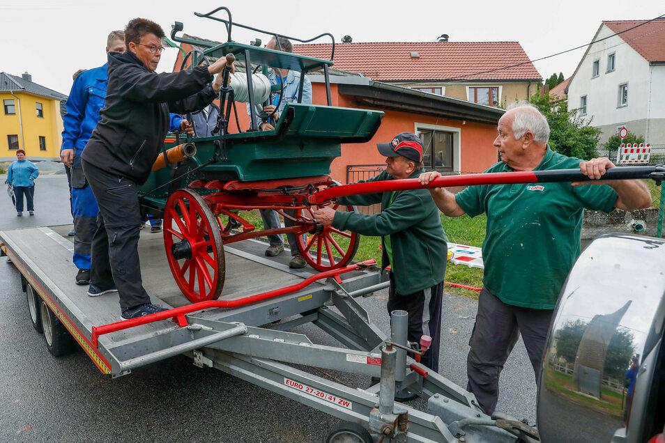 Die Dorfgemeinschaft Calrsbrunn hilft Claus Henkel (rechts) beim Hochhieven der alten Feuerwehrspritze.