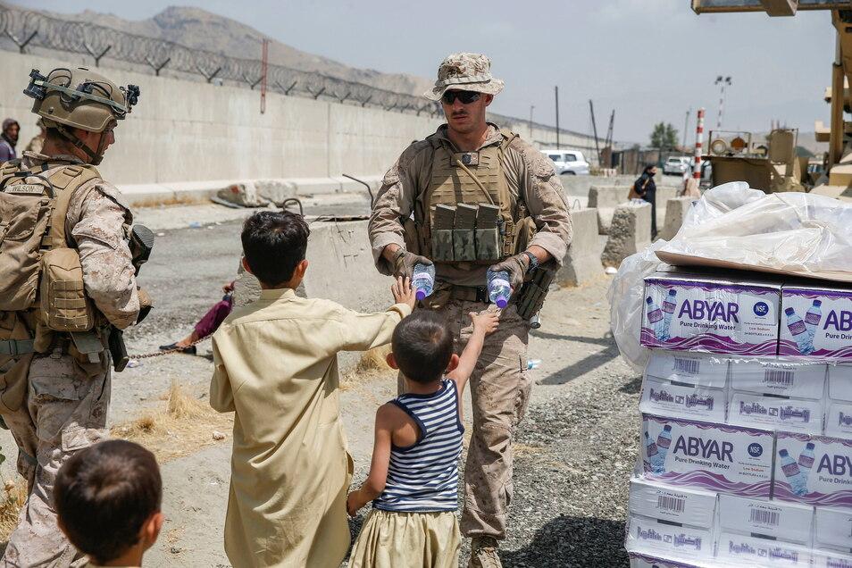 Auf diesem von den US-Marines zur Verfügung gestellten Bild verteilt ein US-Marinesoldat während einer Evakuierung Wasser an Kinder.