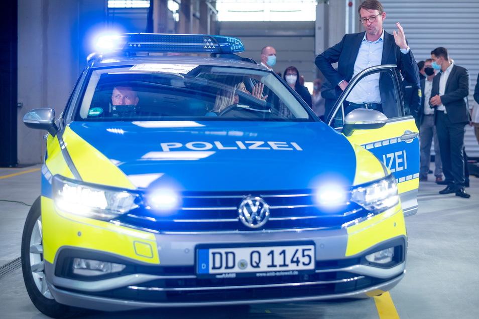 Innenminister Roland Wöller (neben dem Auto stehend) ist bei der Präsentation der neuen Digitaltechnik im Streifenwagen dabei.