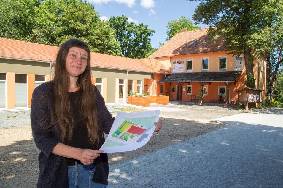 Helen Linde vom Mehrgenerationenhaus zeigt die Pläne für den Spiel-, Sport- und Bewegungsplatz vor dem Objekt. Der Platz soll dieses Jahr noch gebaut werden.
