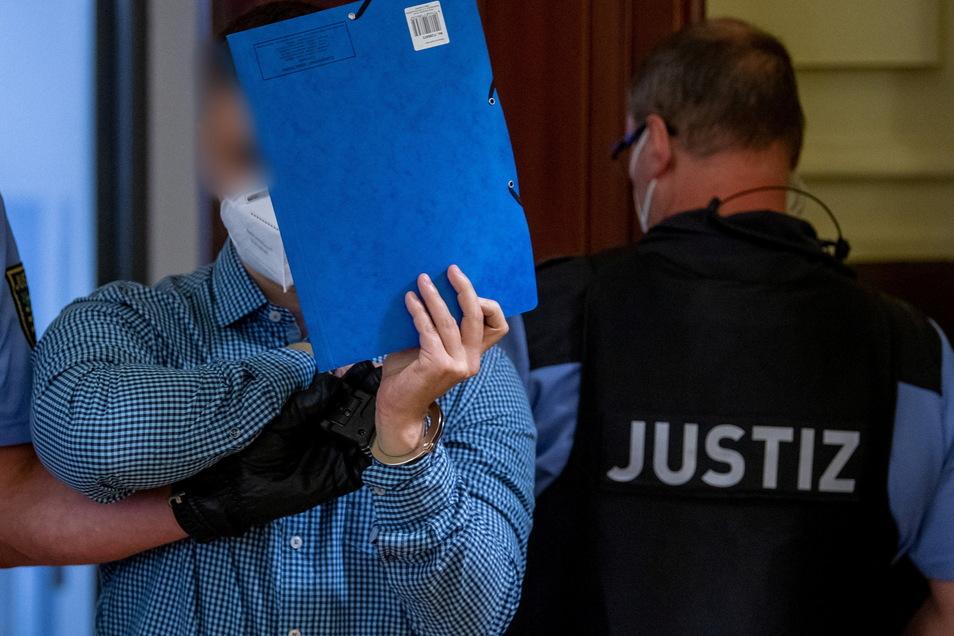 Ein angeklagter Mann wird von Justizpersonal in den Verhandlungssaal in Leipzig geführt. Die Staatsanwaltschaft wirft dem 34 Jahre alten Angeklagten vor, im November 2020 einem 52-Jährigen ein Messer in die Schläfe gerammt zu haben - vor den Augen des