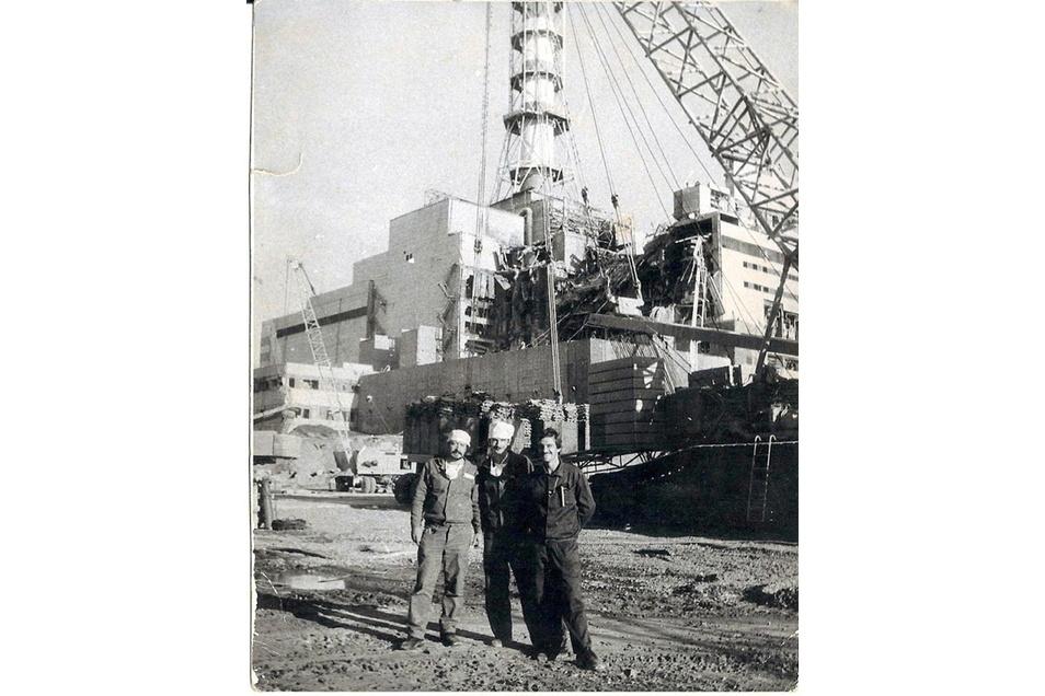 Die Aufnahme, die um den 25. August 1986 entstanden ist, zeigt die erste gut 17 Meter hohe Kaskade des ersten Betonsarkophags am explodierten Block vier des Atomkraftwerks Tschernobyl. Davor steht Ilja Suslow (r.) mit zwei Kollegen für ein Erinnerungsfoto
