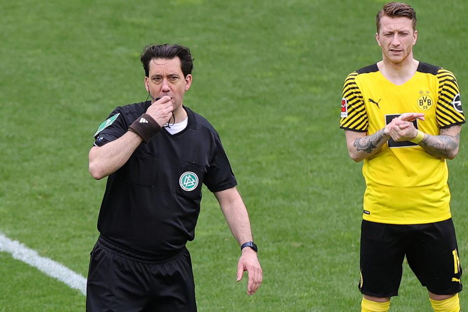 Schiedsrichter Manuel Gräfe (l) pfeift in seinem letzten Spiel, während Dortmunds Marco Reus applaudiert gestikuliert. Gräfte ist 47 Jahre alt und damit laut DFB zu alt für den Job.
