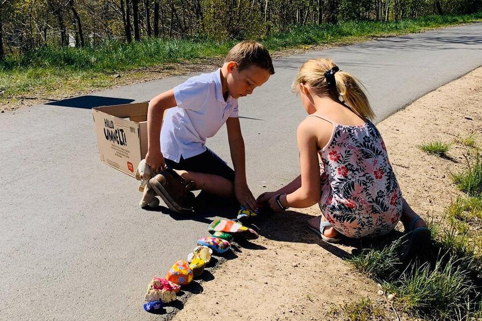Zwei Kinder bemalen Steine und legen eine Schlange im Guido-Brescius-Weg in Freital-Kleinnaundorf.