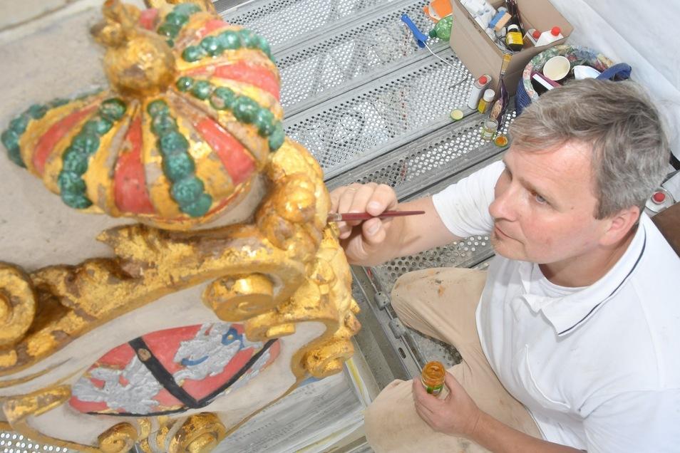 Eine Arbeit für ruhige Hände. Der Maler Michael Donath trägt neues Gold auf die Neustädter Postmeilensäule auf.