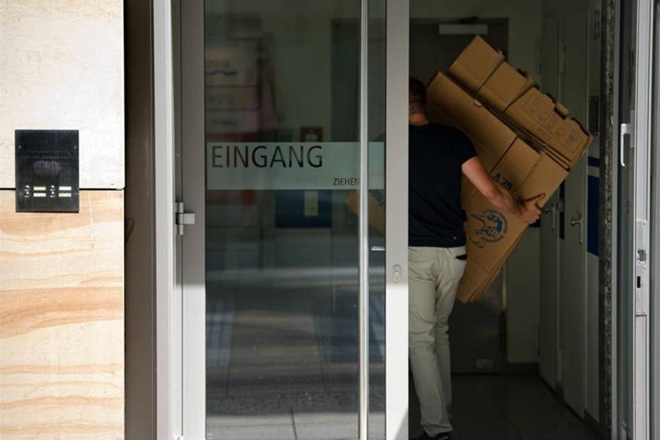 Polizisten tragen Kisten aus den Büros.